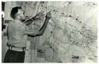 Captain Owers studying a wall map while an Intelligence Officer, Chief Engineers Branch, at Lae-Nadzab in July 1944.