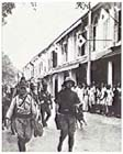 Japanese troops march through Labuan, Borneo 14 January 1942.  The ease with which the Imperial Japanese forces conquered Southeast Asia in early 1942 spurred the Japanese to enlarge upon their original war plan and attempt to isolate Australia.  New Guinea, which had barely figured in pre-war Japanese plans, would now become a key strategic objective.