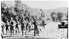 "The band of the newly arrived 2/22nd Battalion with the rest of the unit formed up behind them, about to move off during ANZAC Day commemorations in Rabaul, 25 April 1941.  The 2/22nd Battalion made up the bulk of the New Britain garrison, known as ""Lark Force"".  Of the 24 bandsmen seen here only one would survive the war.  The Battalion as a whole lost 571 men killed, many of whom drowned as prisoners of war of the Japanese when an unmarked transport ship taking them to Japan to work as slave labourers was sunk by an American submarine in the South China Sea in July 1942."
