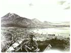Rabaul, September 1945.  The town itself occupies the flat plain while, from left to right, the heights of North Daughter, The Mother and South Daughter dominate the skyline.  Rabaul possessed a large and well-sheltered natural harbour capable of holding up to 300,000 tons of shipping and its strategic value was recognised by both the Australians and the Japanese in the lead up to the Pacific War.