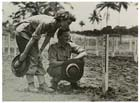 Two Australian nurses inspect the grave marker of Petty Officer 2nd Class NAKAMOTO in the Japanese section of the military cemetery at Lae, November 1944.  In addition to looking after their own dead Australian Army War Graves units were also responsible for creating and maintaining the graves of those Japanese whose bodies were recovered by Allied forces.