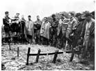 Makeshift wooden crosses mark the graves of three Australian soldiers killed in action near Orodubi, New Guinea, 29 July 1943.  A Catholic priest (second from left) conducts the burial service surrounded by the dead men's comrades, one of whom is covering the priest's prayerbook with his groundsheet to protect it from the rain.